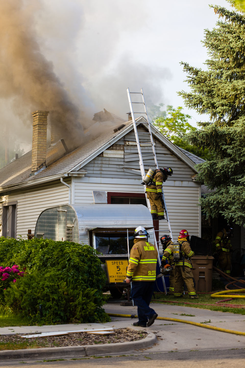 Fire fighters combat a house fire