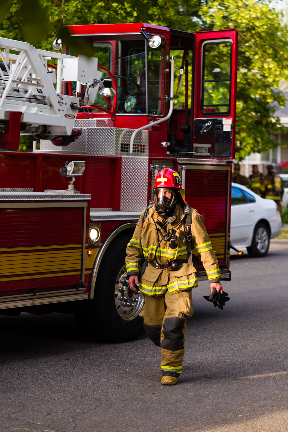 A fire fighter walks through the fire trucks
