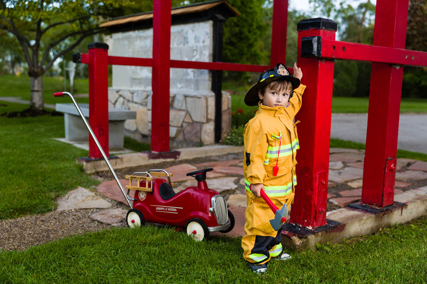 Alexander is dressed as a fire fighter and has a Radio Flyer Fire Truck