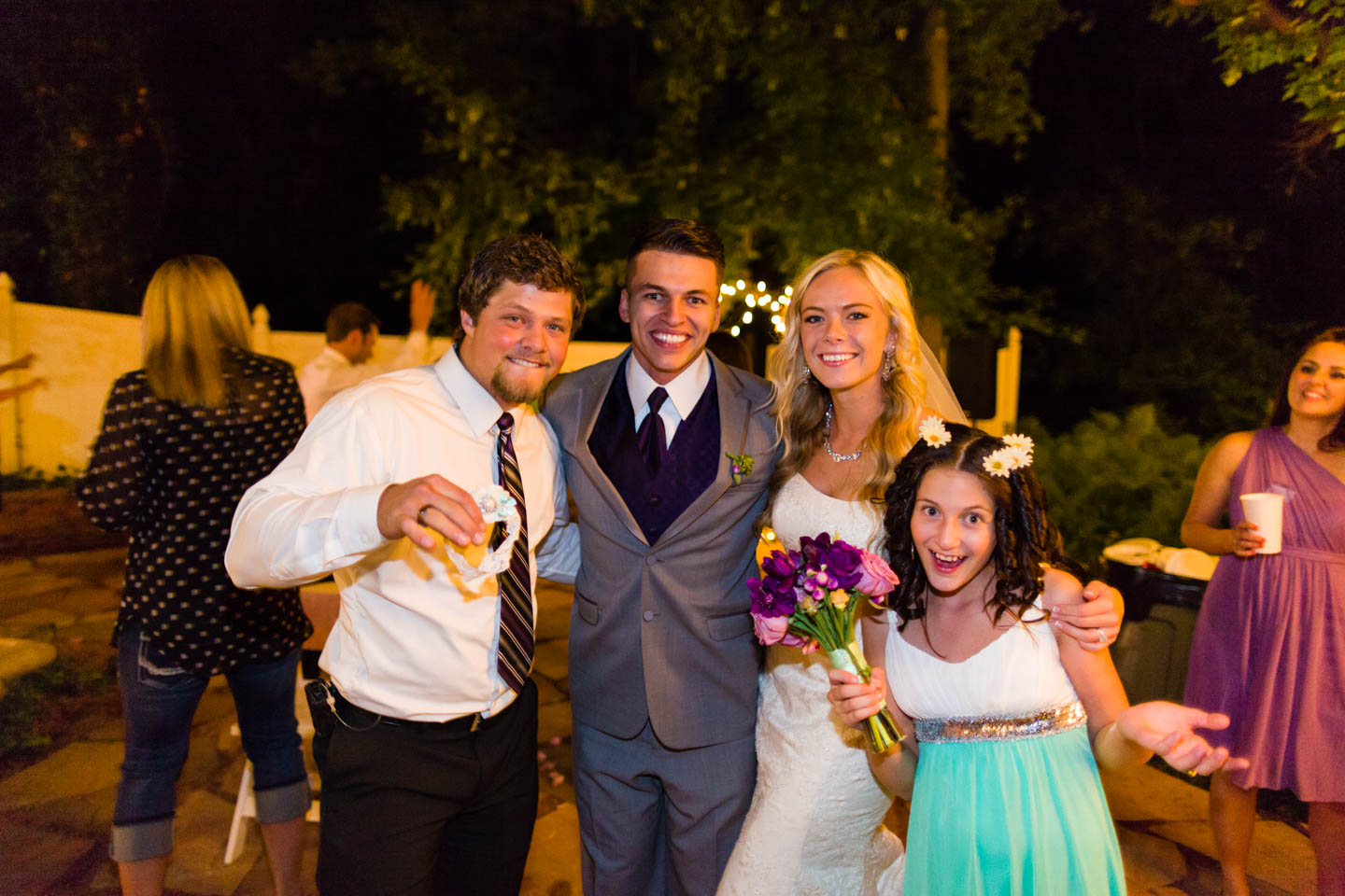 Bride and groom pose with the people who caught the garter and wedding bouquet