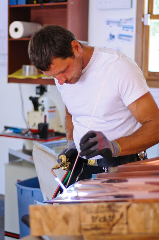 Erno welds copper finials in his workshop