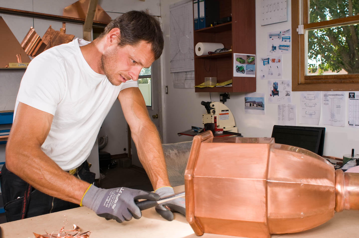 Erno works on copper finials in his workshop