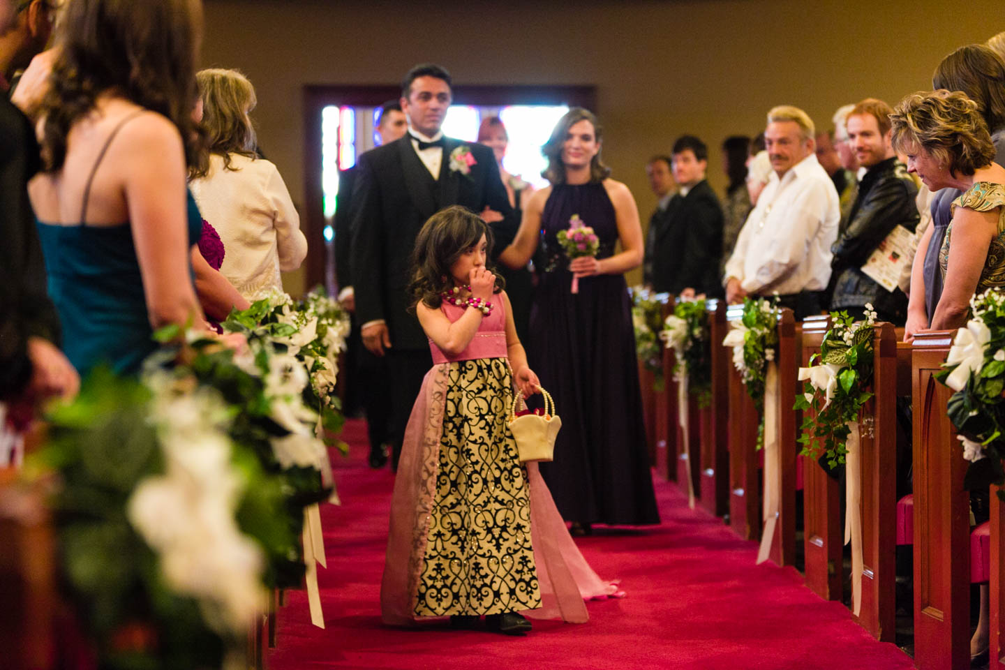 The flower girl walking down the aisle and forgets to throw some flower petals