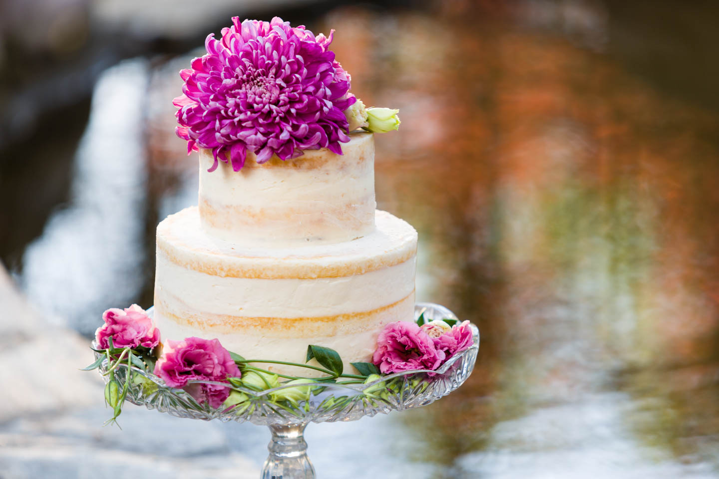 Spring wedding cake with flowers. Cake next to a pond.