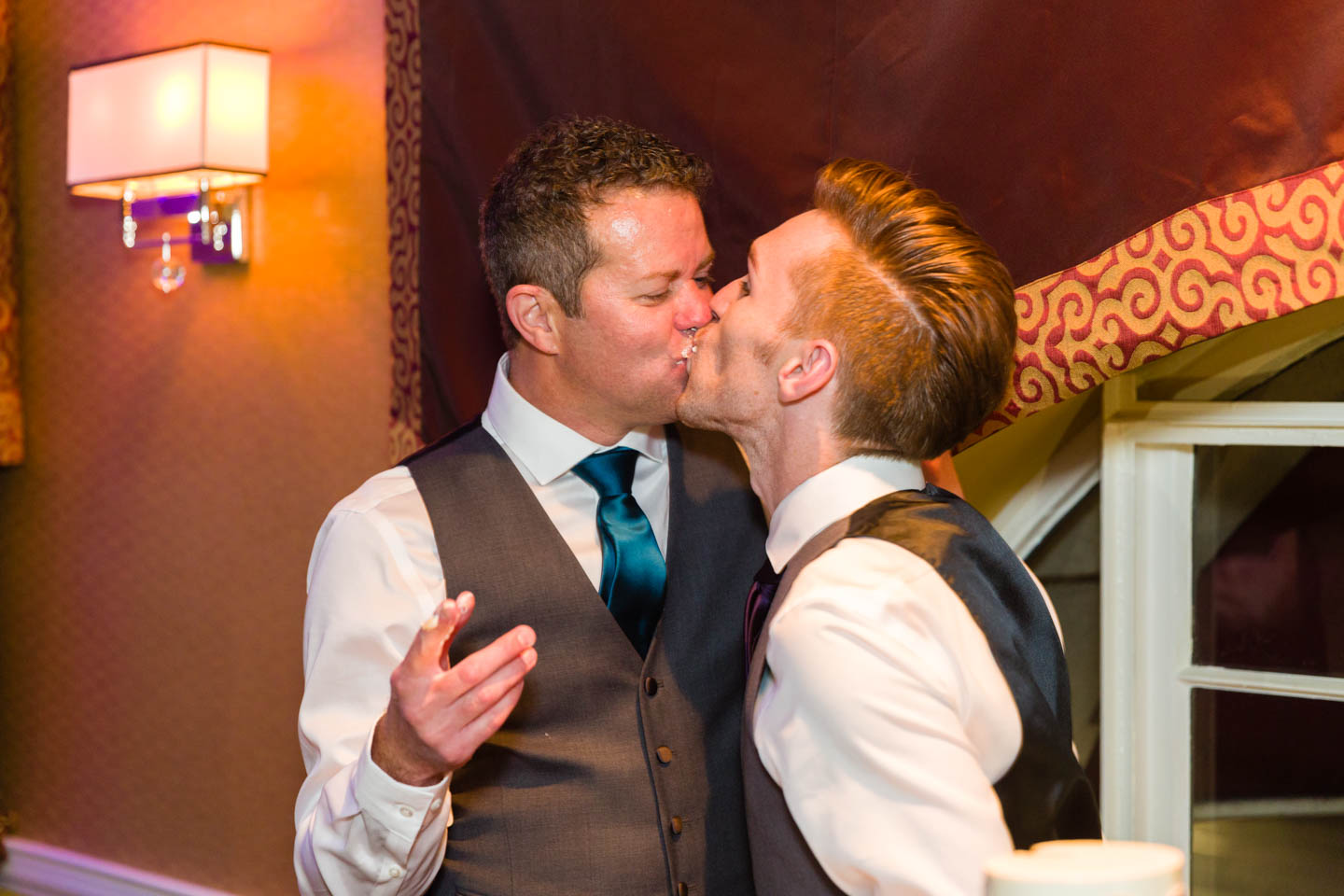 Grooms kiss after cutting the wedding cake