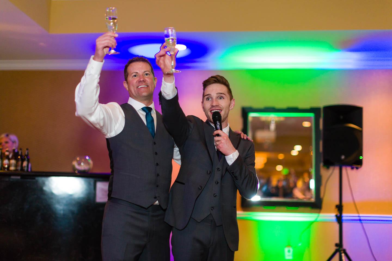 Grooms toast the wedding reception