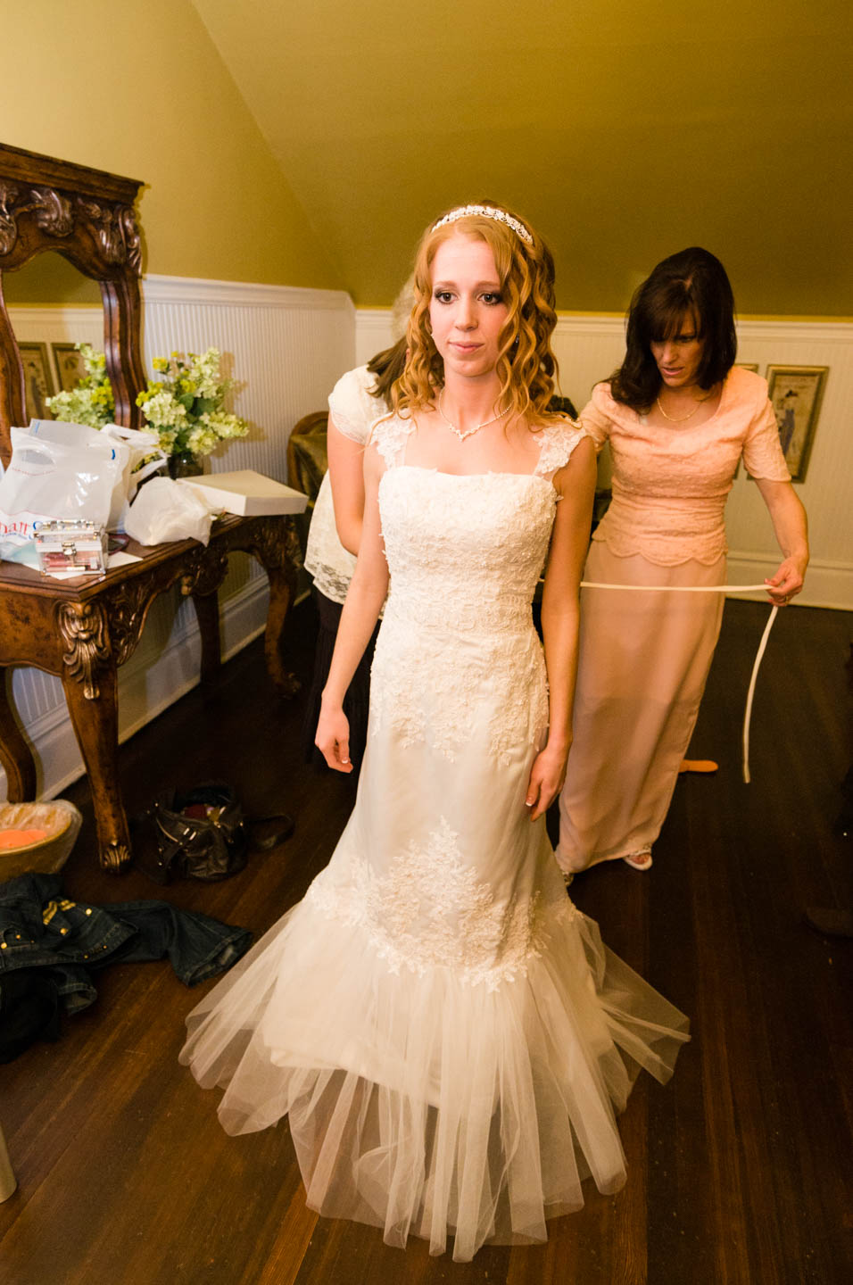 Bride puts on her wedding dress