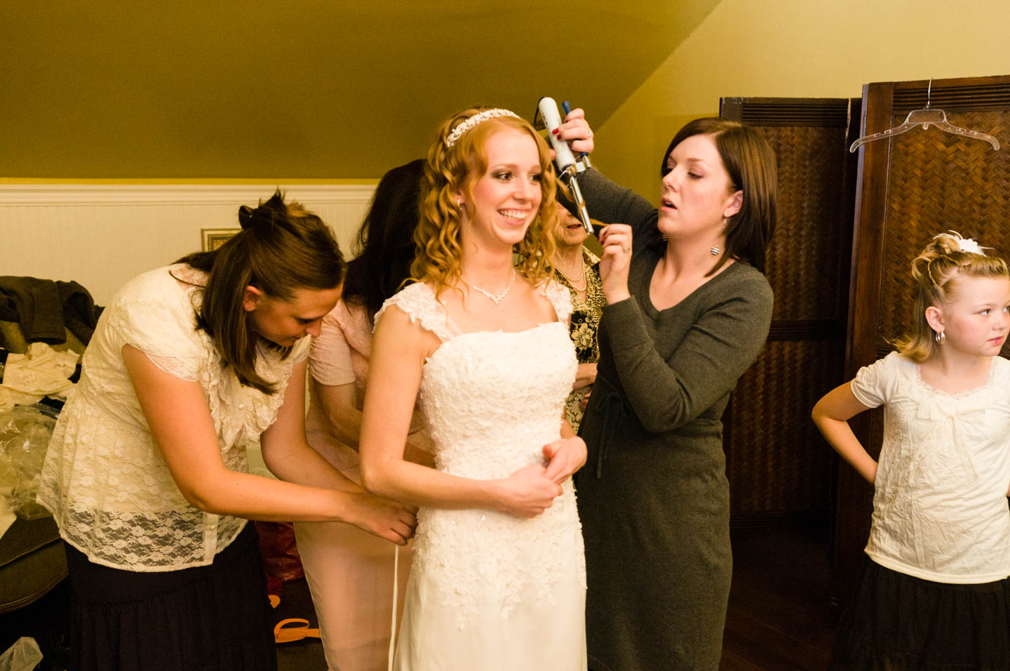 Bride receives the finishing touches to dress and hair