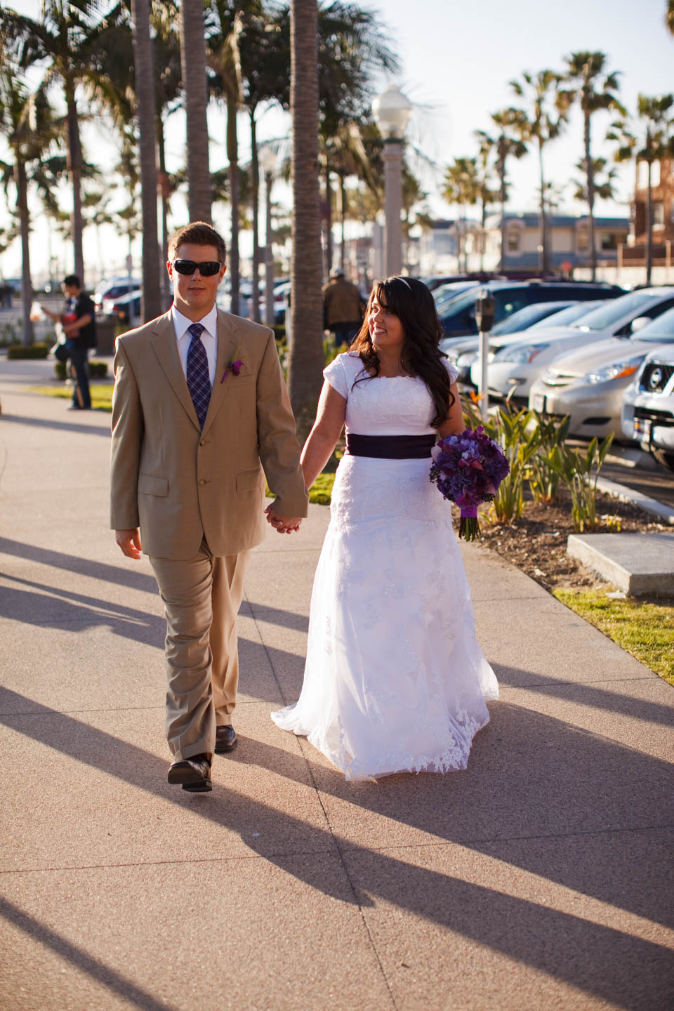 Bride and groom walk the boardwalk to the reception